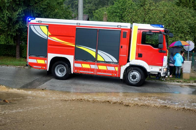 Fire department rushes to rescue when floods hit village in Europe after heavy rain. Red fire brigade engine,firefighting truck and firefighters rush to rescue royalty free stock photography