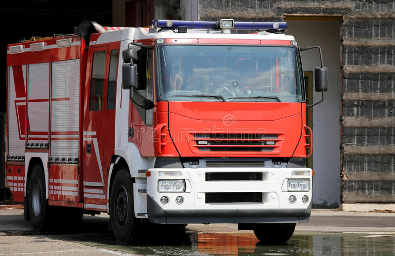 Red fire engine truck during a fire drill. One fire engine truck during a fire drill in the fire brigade station royalty free stock photography