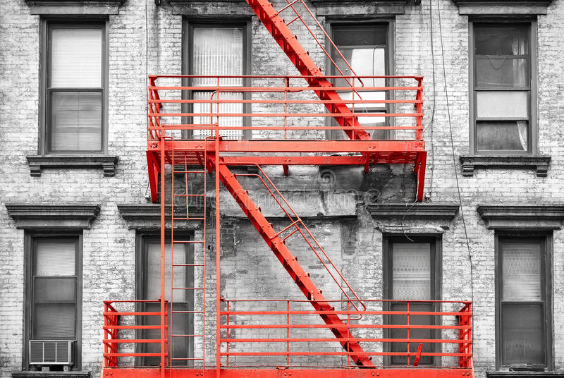 Red fire escape at black and white filtered residential building stock photos