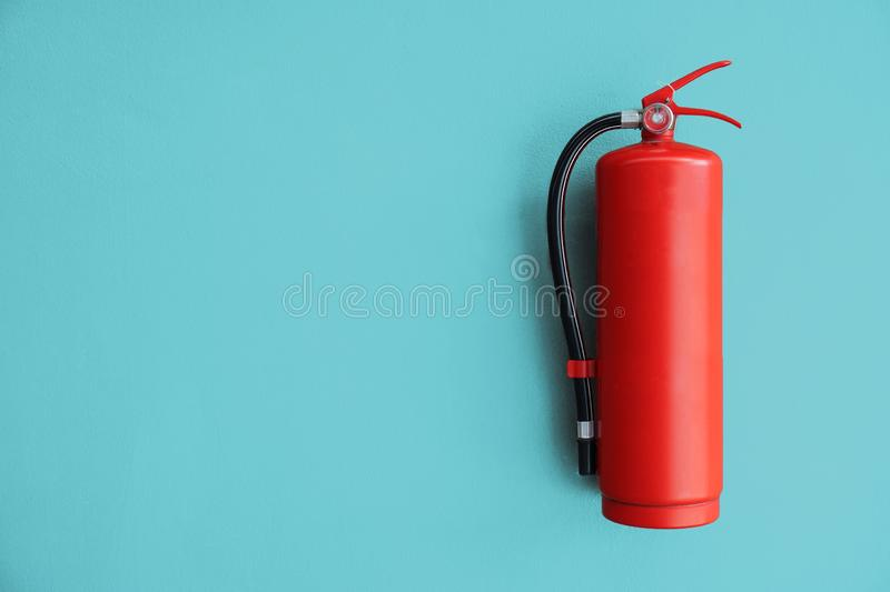 Red Fire extinguisher on the blue wall. Red Fire extinguisher on the blue wall stock image
