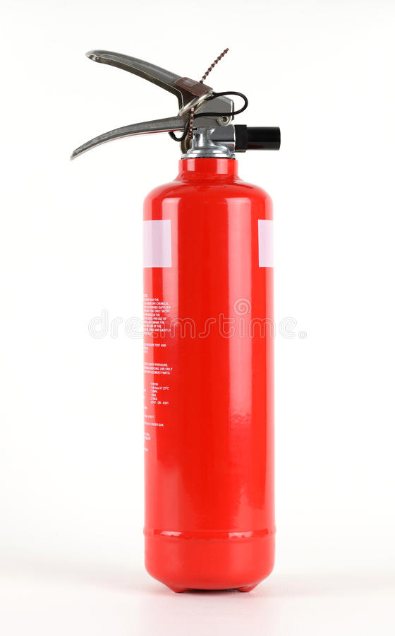 Red fire extinguisher. A red fire extinguisher with safety tab attached royalty free stock images