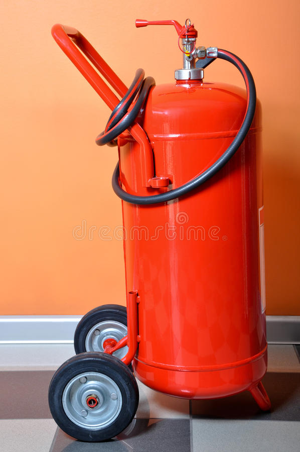 Red fire extinguisher. Standing by the wall royalty free stock photography