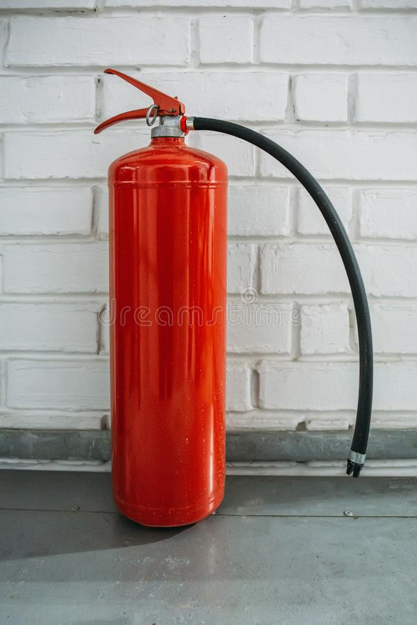 Red fire extinguisher stands on floor near white brick wall stock images