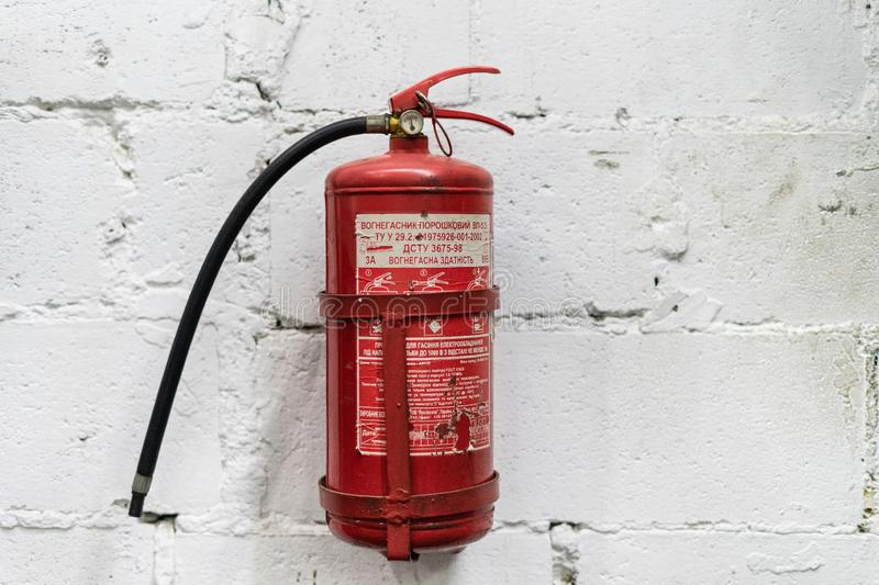 Red fire extinguisher. On white wall background, ready to use stock photos