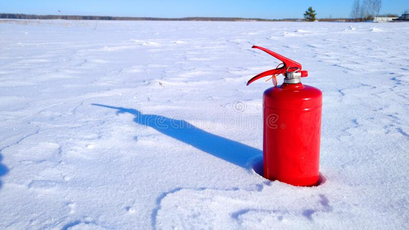 Red fire extinguisher on a winter surface of white shiny snow with a shadow from snow drifts stock photos