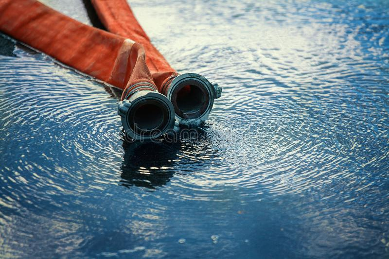 Red fire hose lying in a puddle of water. Fire fighting theme with space to copy.  royalty free stock photos