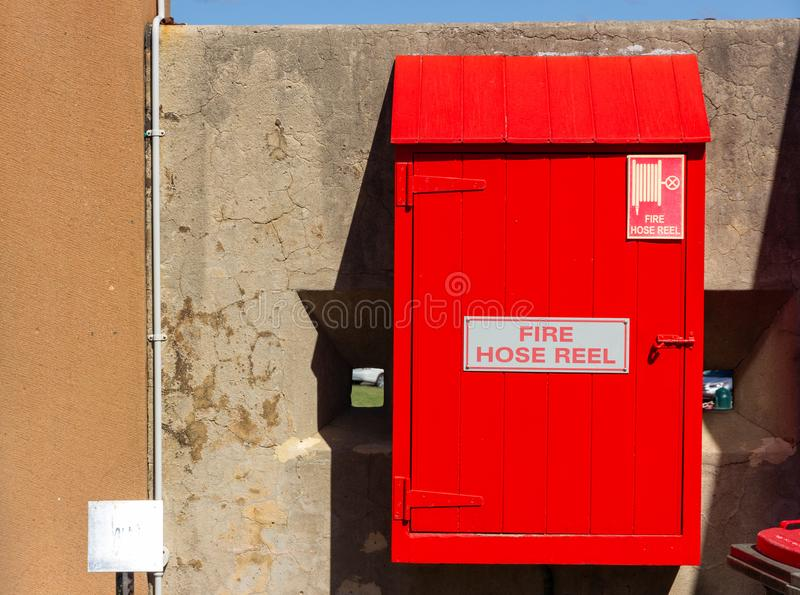 Red fire hose reel, mounted on old concrete wall background. Red fire hose reel , mounted on old concrete wall background stock images
