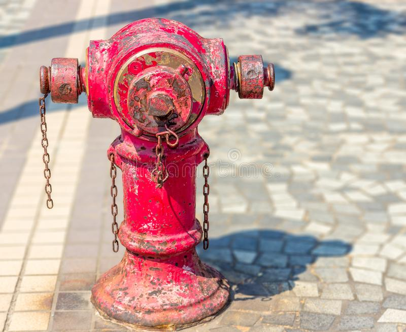 Red fire hydrant in Hong Kong. Typical old red fire hydrant with rusty chains on the sidewalk in Hong Kong city on a sunny day stock photography