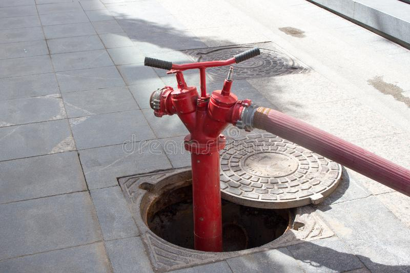 Red Fire Hydrant in Moscow. A fire hydrant, fire pump, johnny pump, or simply pump, is a connection point by which firefighters can tap into a water supply stock photo