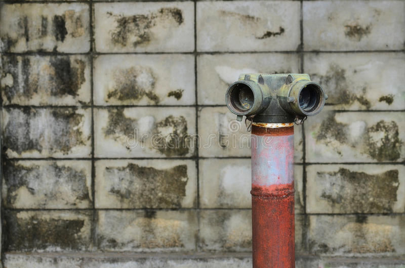 Red fire hydrant. Near a cement wall royalty free stock photos