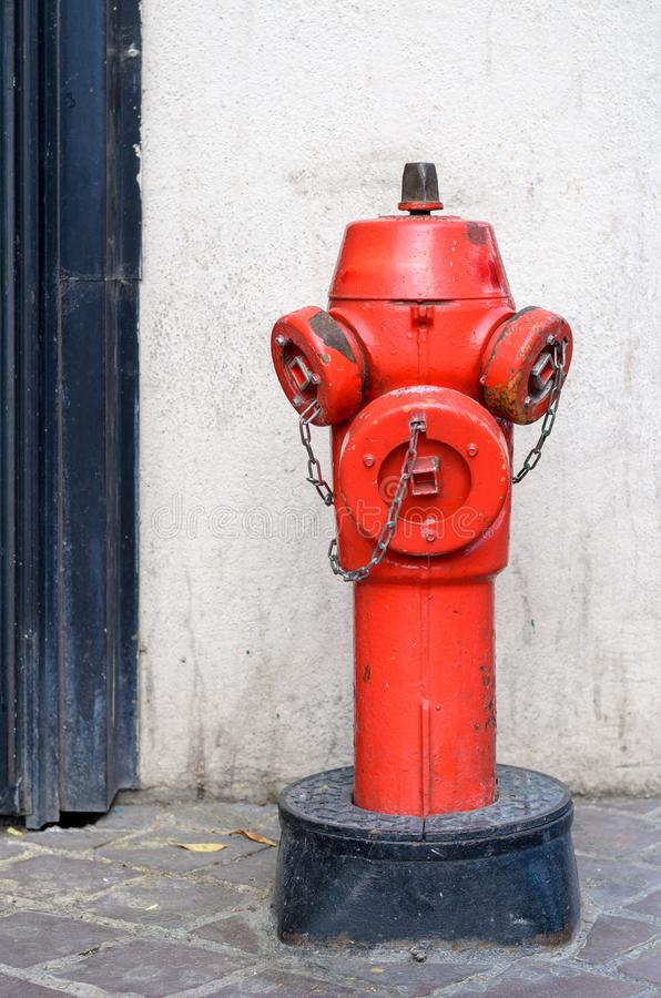 Red fire hydrant on a paved sidewalk. To the side of a door frame for supplying water in times of a fire fighting emergency royalty free stock photo