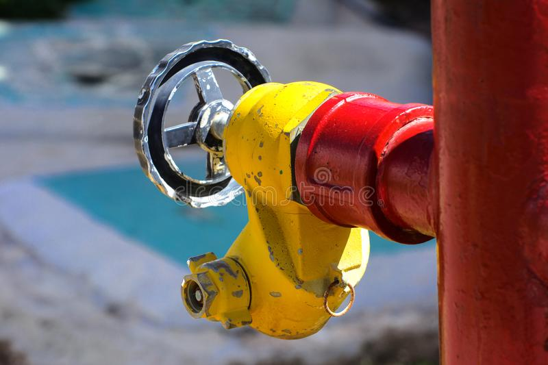 Red fire hydrant with yellow connectors. Fire hydrant or fire pump, represents the point of connection, through which firefighters. Can enter the water supply stock image