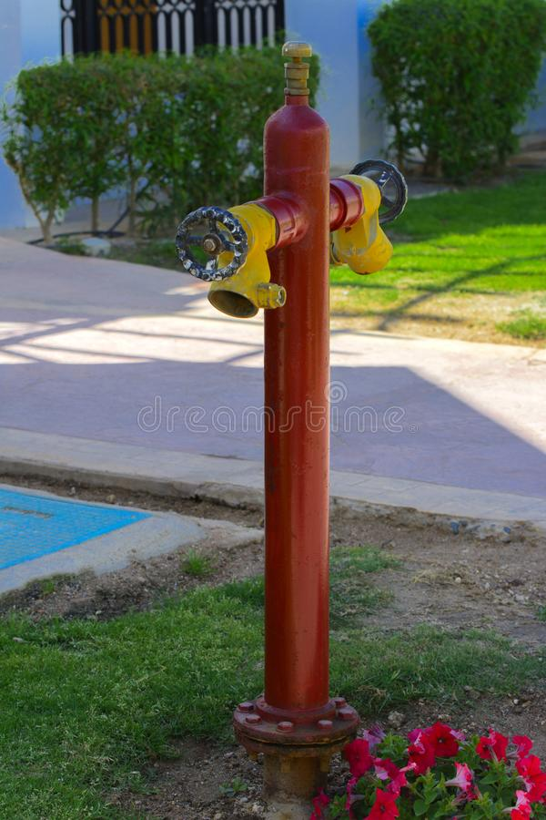 Red fire hydrant with yellow connectors. Fire hydrant or fire pump, represents the point of connection, through which firefighters. Can enter the water supply royalty free stock photography