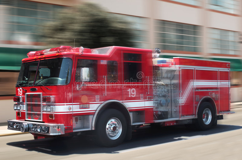Red fire truck. Rushing down street stock images
