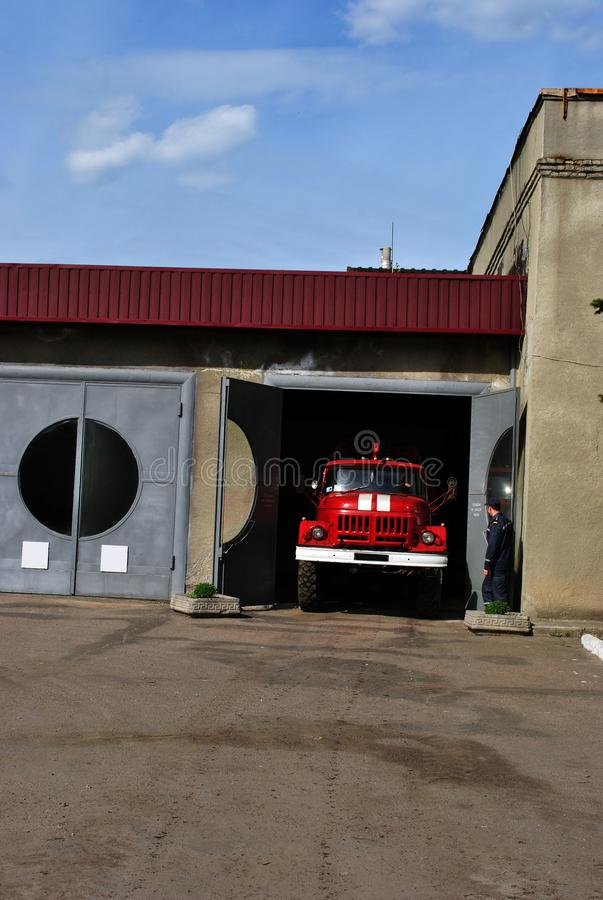 Red fire truck rides from the garage to emergency call, open gate with guard. Against a background of a spring blue sky royalty free stock images