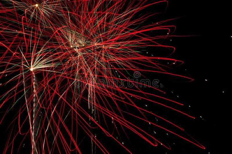 Red Firebursts in the evening sky. Red rockets explode in the night sky stock image
