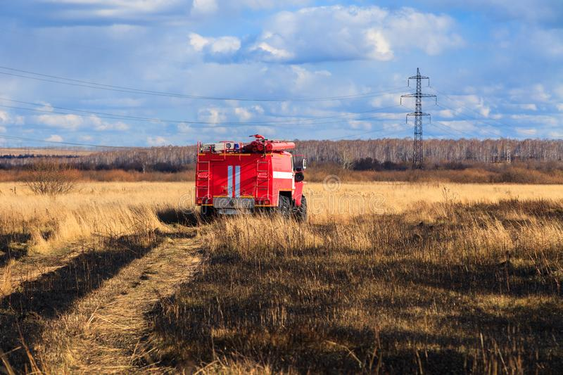 Red firetruck car Ural rides through the autumn field with yellow and faded grass against the blue sky and clouds. The concept. Of extinguishing forest fires in stock photo