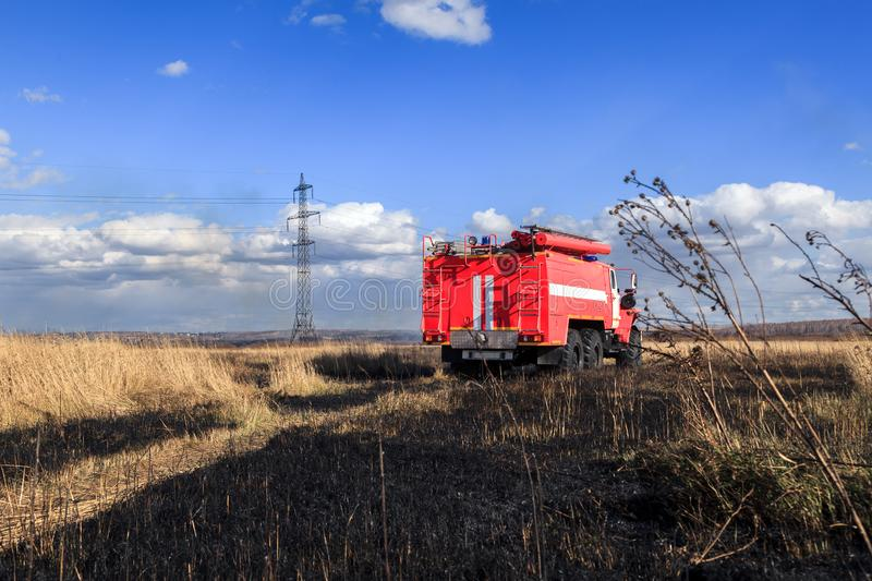 Red firetruck car Ural rides through the autumn field with yellow and faded grass against the blue sky and clouds. The concept. Of extinguishing forest fires in royalty free stock photo