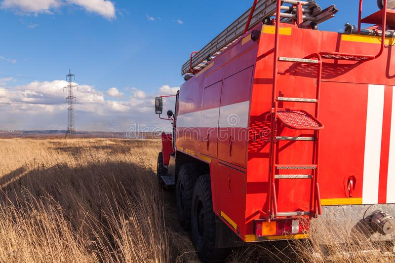 Red firetruck car Ural rides through the autumn field with yellow and faded grass against the blue sky and clouds. The concept. Of extinguishing forest fires in royalty free stock photography