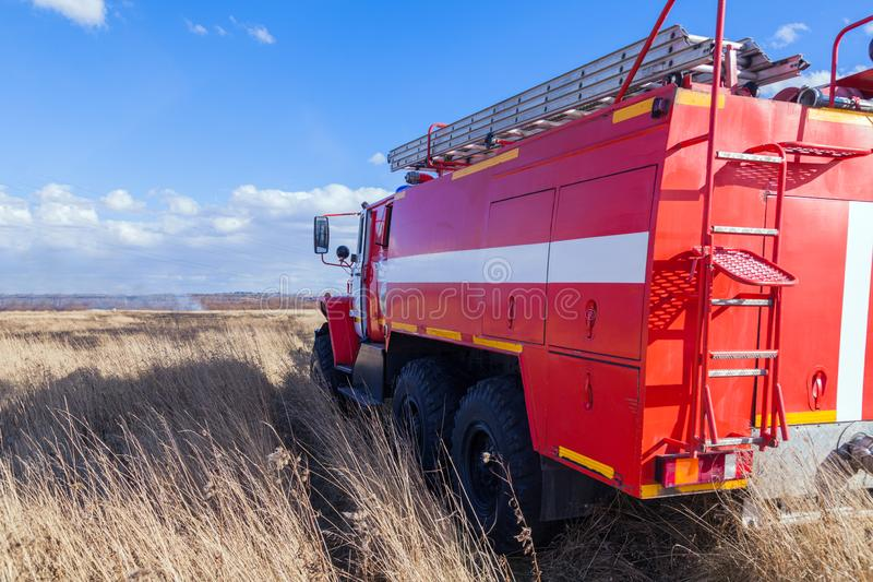Red firetruck car Ural rides through the autumn field with yellow and faded grass against the blue sky and clouds. The concept. Of extinguishing forest fires in stock photos