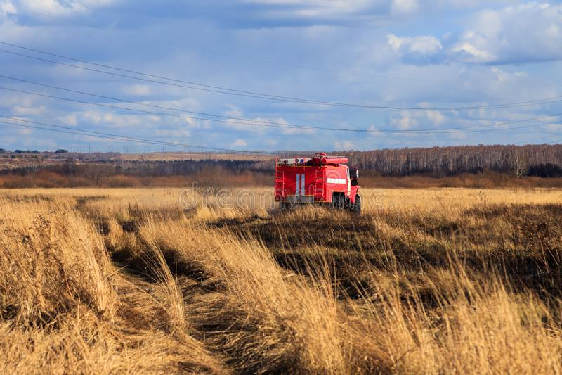 Red firetruck car Ural rides through the autumn field with yellow and faded grass against the blue sky and clouds. The concept. Of extinguishing forest fires in stock image