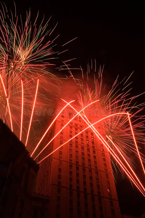 Red fireworks around a tall building stock photos