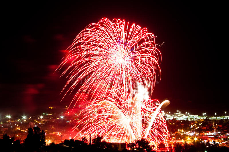 Red fireworks at night. Ref fireworks over a city at night stock photo
