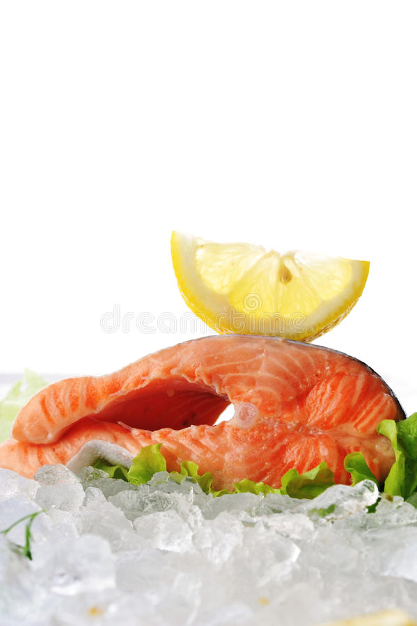 Red fish on ice. Pieces of red fish and lemon on ice stock image
