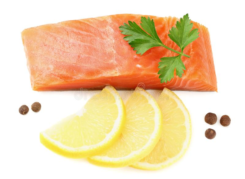 Red fish. Raw salmon fillet with parsley, peppercorns and lemon isolate on white background. Top view stock photography