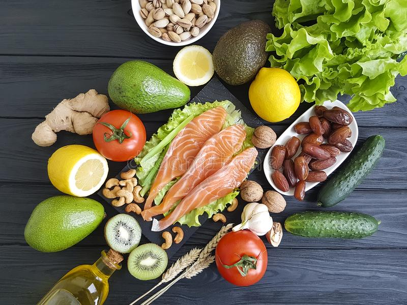 Salmon fish, avocado organic green dietary on a wooden healthy food assorted. Red fish salmon, avocado on wooden healthy food dates assorted organic dietary royalty free stock photos