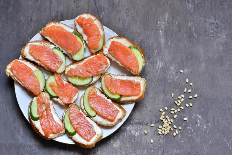 Red fish sandwiches with soft cheese and fresh cucumber on a white plate on a shabby vintage background royalty free stock images
