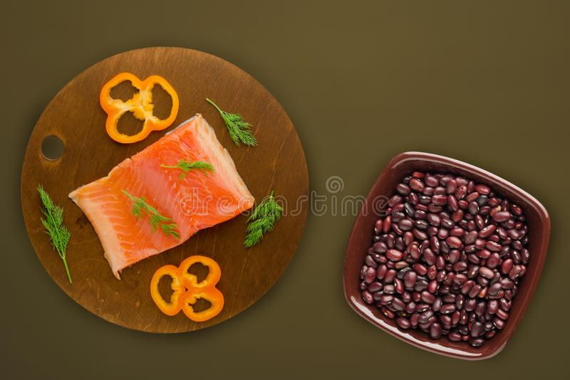 Red fish trout fillets on a brown wooden plate. fish trout on a brown green background. trout with dill, lemon and peppe royalty free stock image