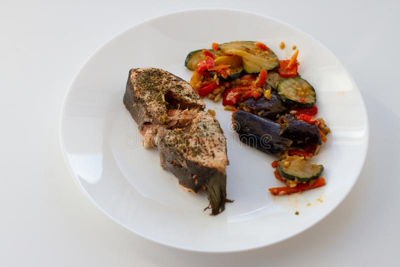Red fish with vegetables on white dish. And white background royalty free stock photography