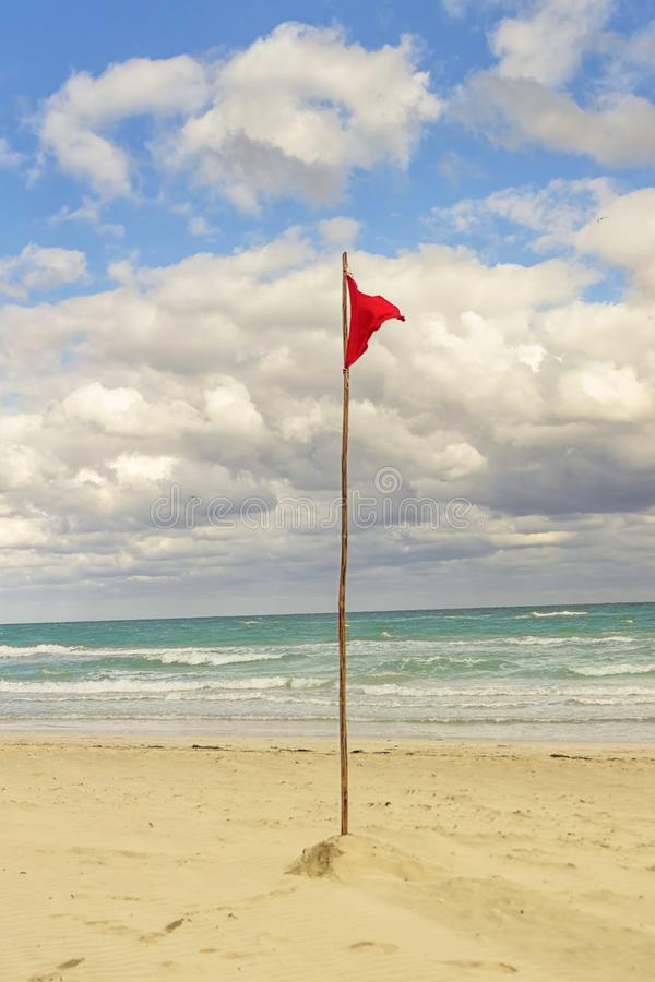 Red flag on the beach prohibiting bathing and entering the water. Close-up royalty free stock image