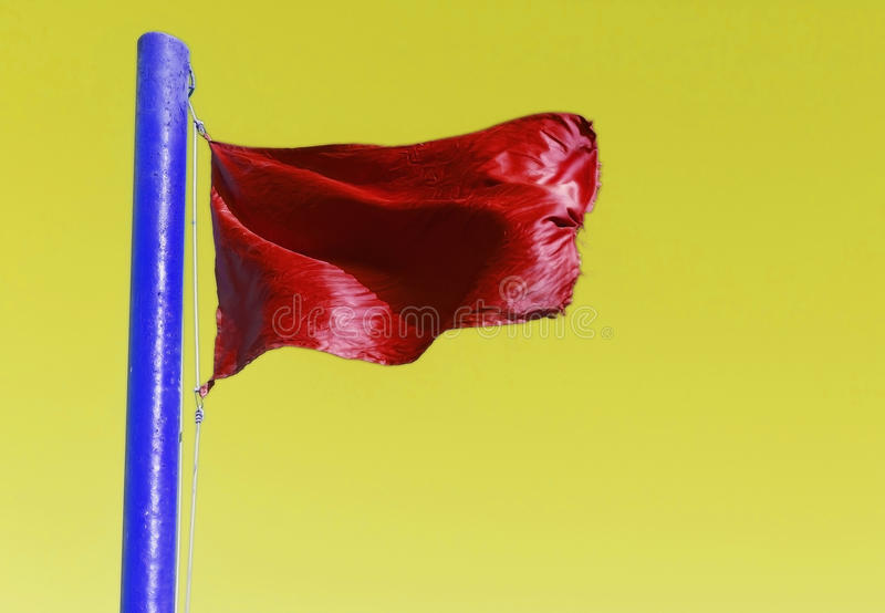 Red flag on the flagpole blue on a yellow background stock photos