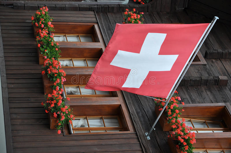 Red flag with geranium, andermatt. Foreshortening of ancient building wooden facade with geranium and red swiss flag royalty free stock images