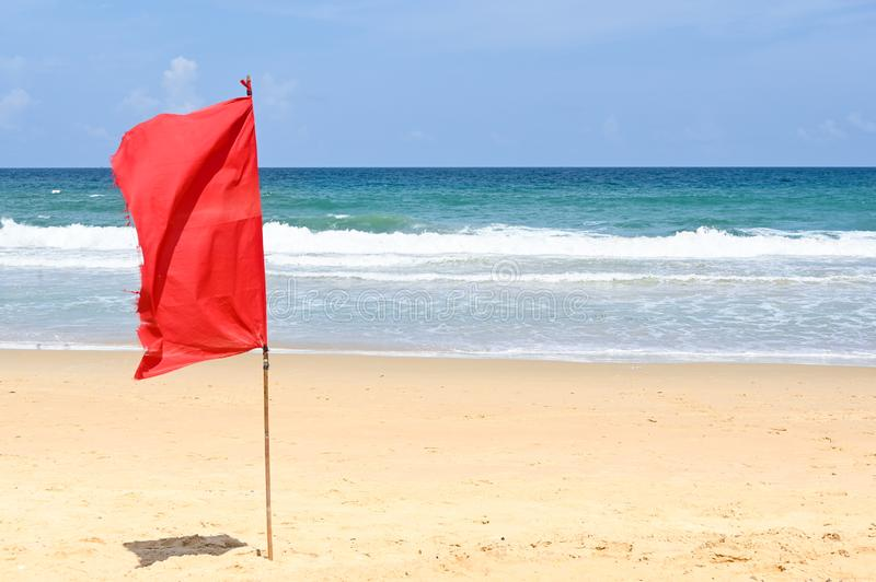 Karon beach with red flag. Phuket, Thailand royalty free stock photography