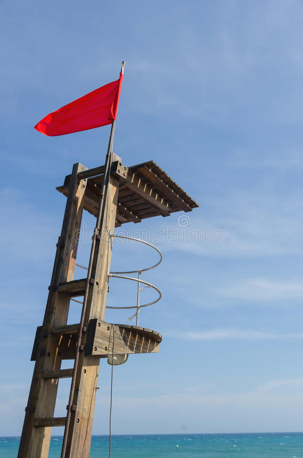 Red flag at lifeguard post. View on lifeguard post with warning red flag against of blue sky royalty free stock photo