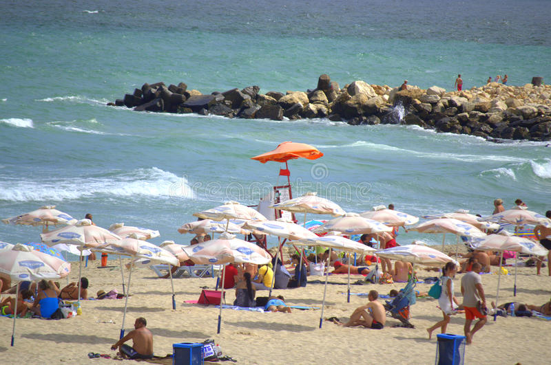 Red flag on summer beach. Vacationing people on red flag summer beach by rough sea,Varna.Bulgaria stock image