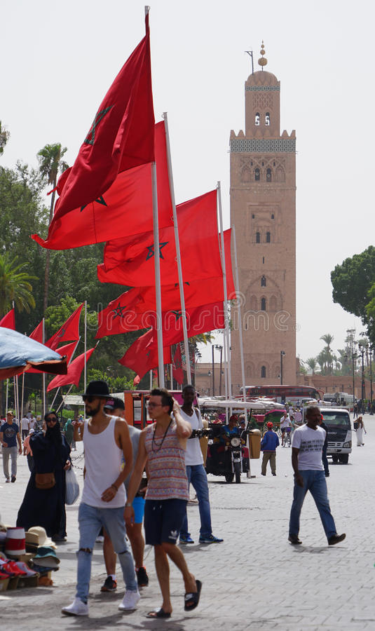 Red flags and the mosque in Marrakech. Marrakesh MoroccoThe Kutubiyya Mosque Arabic: جامع الكتبية, Jāmi` al-Kutubiyya is royalty free stock photos