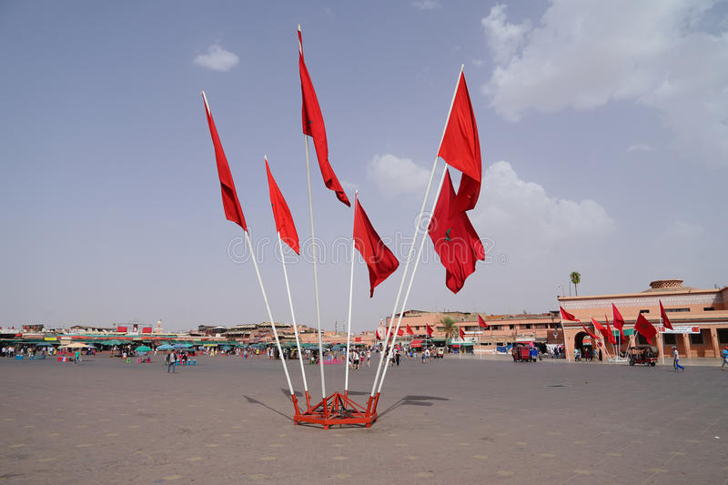 Red flags with the symbol of the five-pointed star waving in the Jamaâna el-Fna square in Marrakech. Marrakesh Morocco Jamaa el Fna in Arabic royalty free stock images