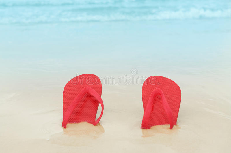 Red flip flops on the beach. Sand.Concept of summer vacations stock photography
