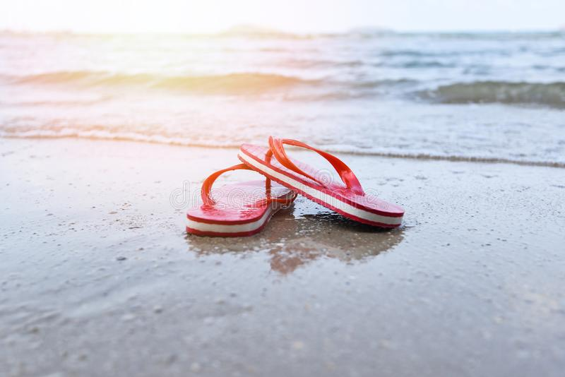 Red flip flops on beach with sandy beach sea ocean and sunlight background stock images