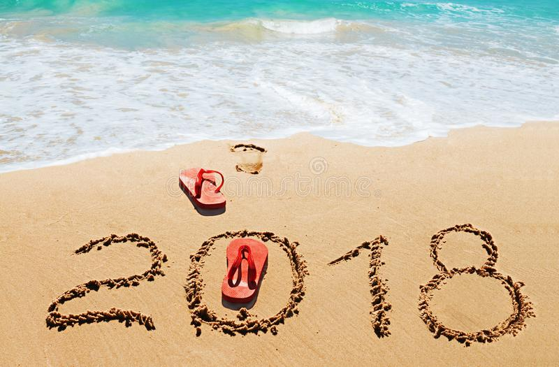 Red flip flops and digits 2018 on the beach. Sand.Concept of summer vacations, new year and Christmas royalty free stock photography