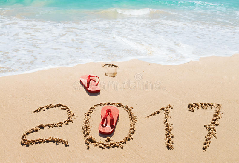 Red flip flops and digits 2017 on the beach. Sand.Concept of summer vacations, new year and Christmas stock photos