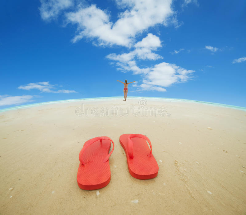 Red flip flops on the beach. Red flip flops and female silhouette on the beach.Concept of summer vacations royalty free stock photos