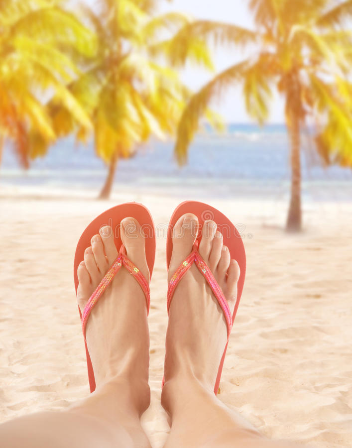 Red flip flops on sandy beach. Close-up royalty free stock images