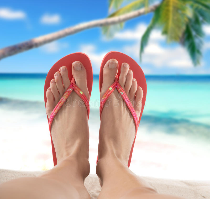 Red flip flops on sandy beach. Close-up stock image