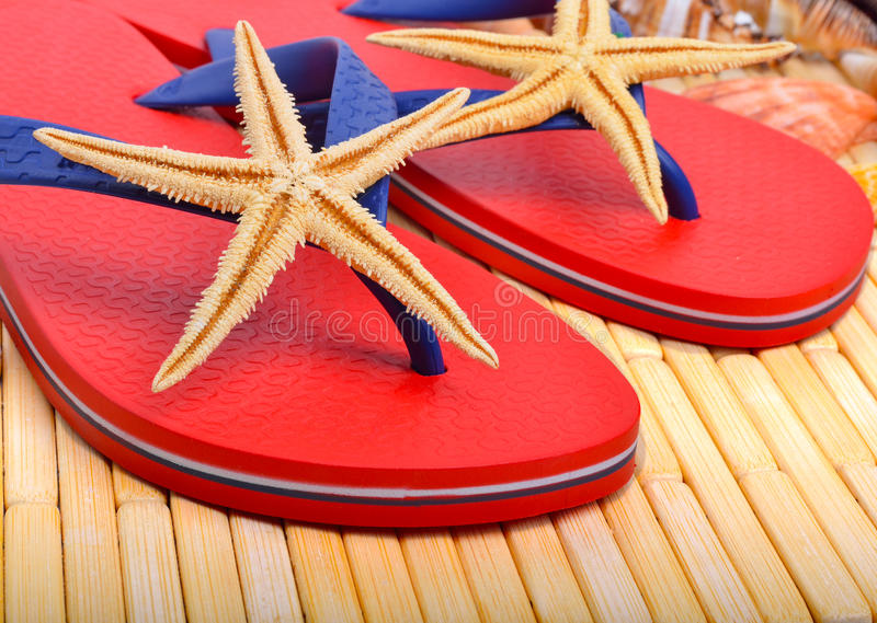 Red flip-flops with starfishes. On a wooden background stock images