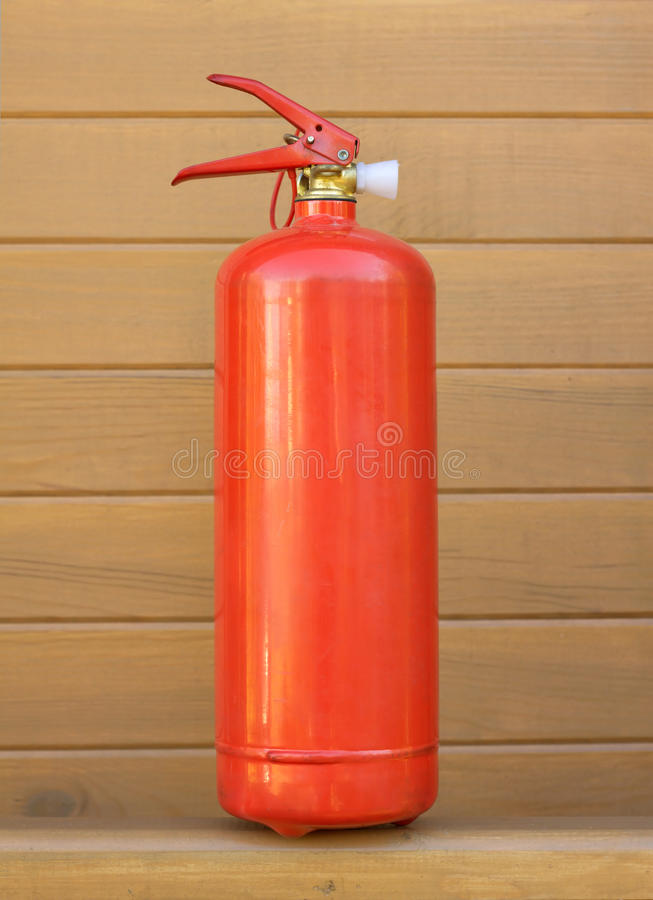 Red Foam Extinguisher Over Brown Wall Royalty Free Stock Images
